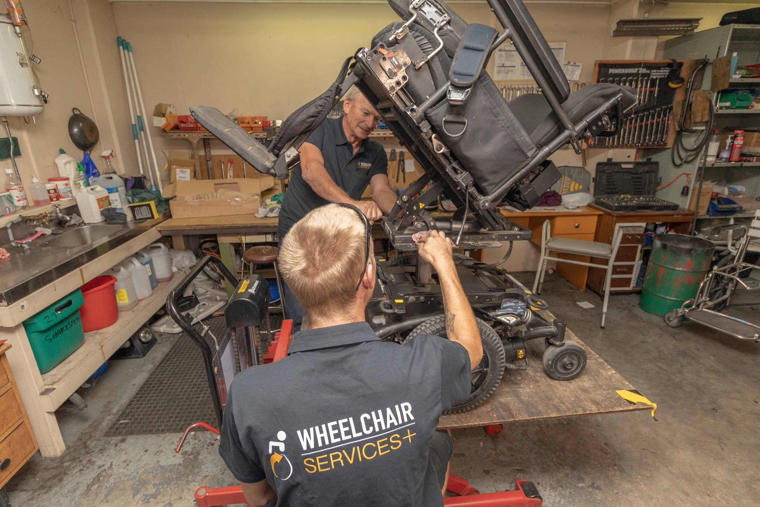 two men repairing and servicing a motorised wheelchair