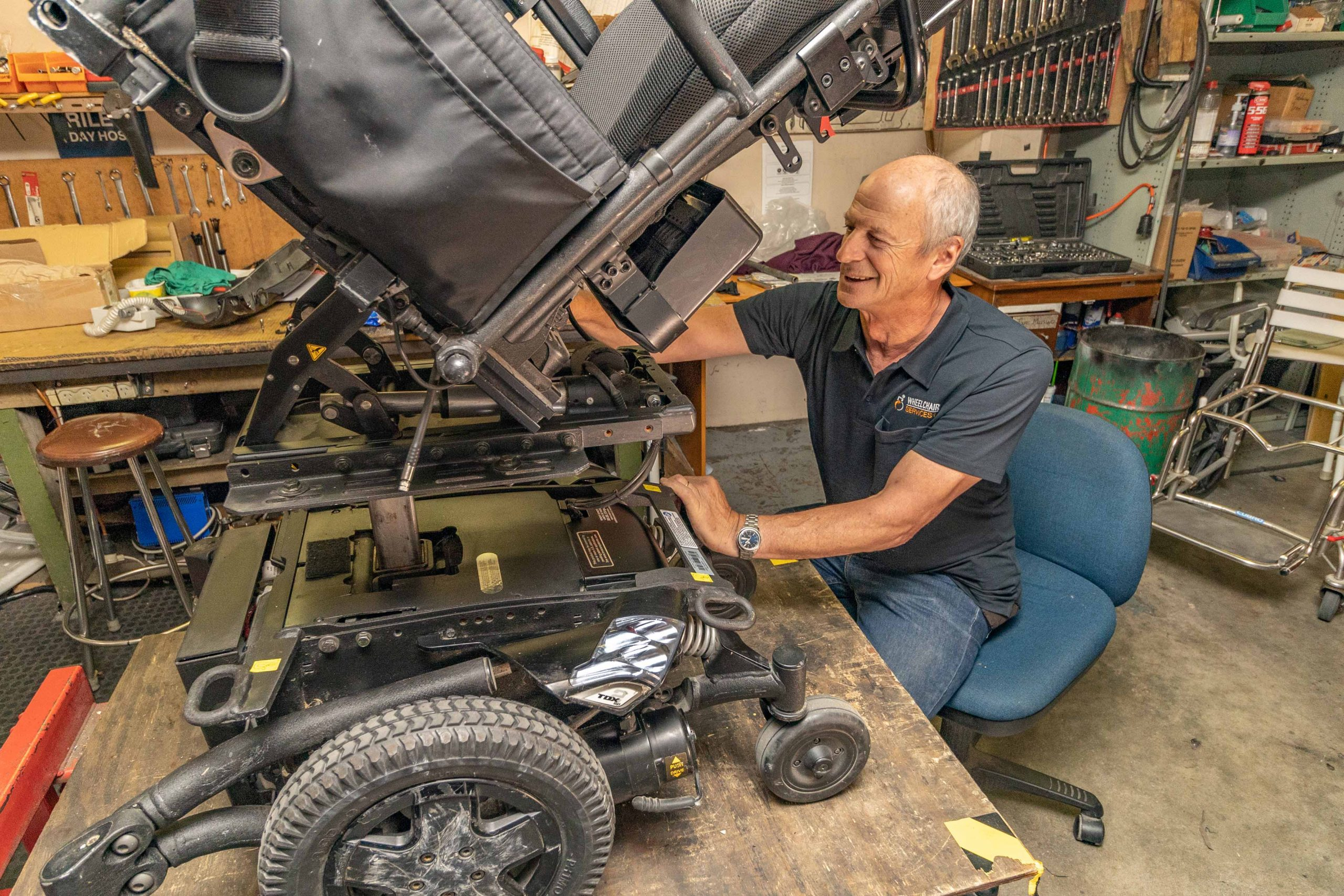 man on chair doing a repair to a motorised wheelchair on a work bench