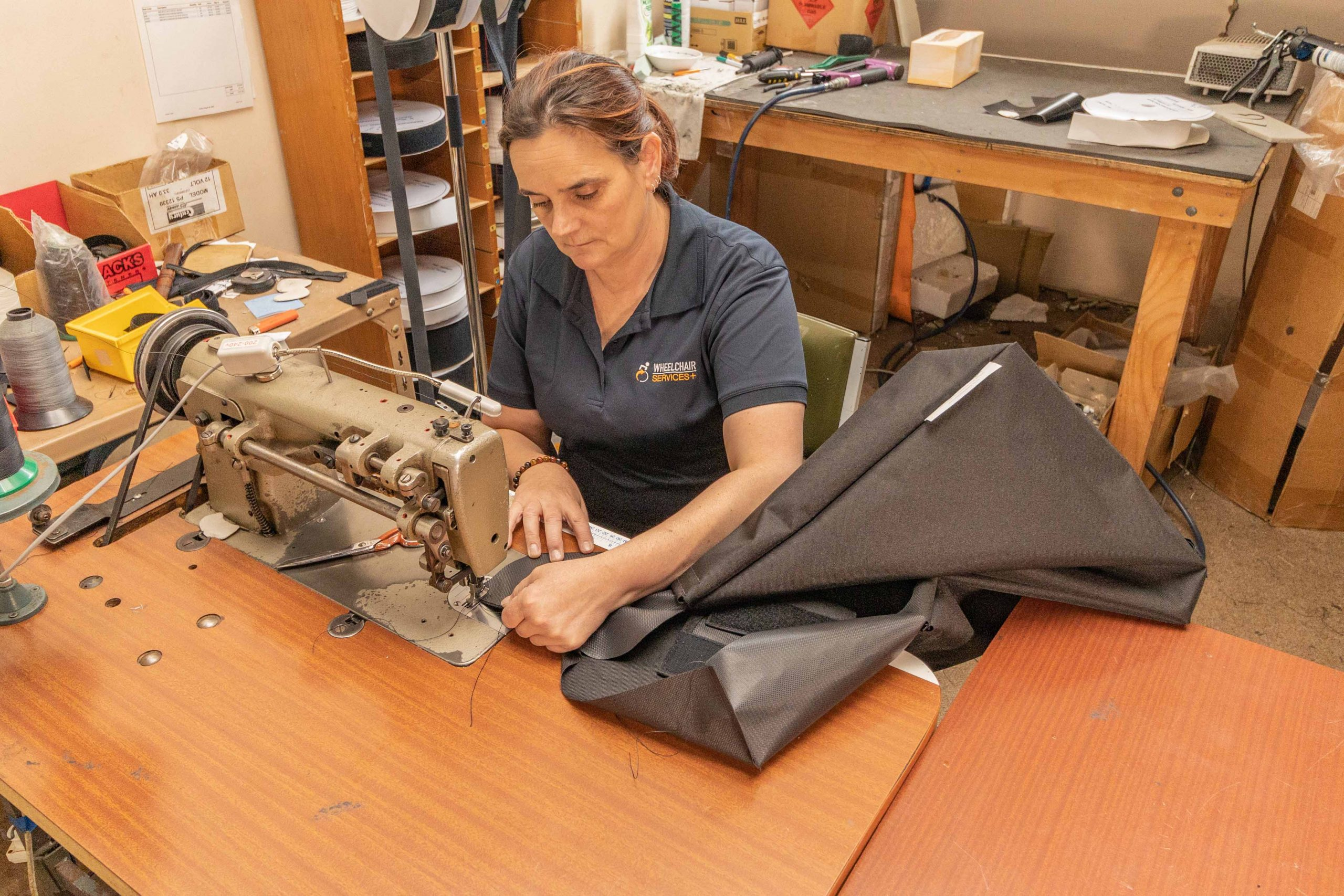woman sitting behind a swing machine sewing black leather upholstery for specialised seating